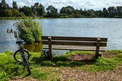 Bicycle near bench and pond in park Stock Image