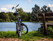 Bicycle near bench and pond in park Stock Photo
