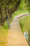 bicycle near river in park/bicycle in park near a reservoir stock photo