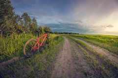 Bicycle near the road in the field at sunset stock photos