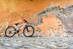 Bicycle near a stone wall. White Bicycle near a stone wall, without a bicyclist Stock Photo