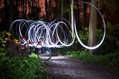 Bicycle in the night forest against the background of a chaotic moving light. Bicycle in the night forest against the backdrop of a chaotic moving light Royalty Free Stock Images