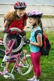 Bicycle o pneu que bombeia pela bicicleta do reparo da menina do ciclista da criança na estrada Foto de Stock Royalty Free