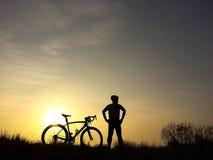Bicycle o suporte do cavaleiro no monte que olha a luz solar e relaxe Foto de Stock Royalty Free