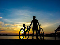 Bicycle o suporte do cavaleiro no rio que olha a luz solar e relaxe Foto de Stock
