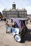 Bicycle o táxi no quadrado da represa na frente do palácio real de Amsterdão fotos de stock