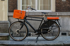 Bicycle with Orange Accents. A vintage bicycle with orange accents is parked on a street sidewalk in the Netherlands stock image
