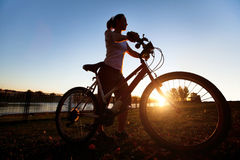 Bicycle outdoor, silhouette. Silhouette of young woman with bicycle outdoor Royalty Free Stock Images