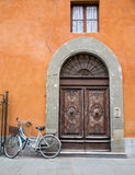 Bicycle Outside Brown Doors on Orange Plaster Royalty Free Stock Images