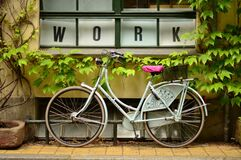 Bicycle Outside Window with Work Sign Stock Photography