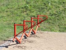 Bicycle park. Metal orange handrails for parking bicycles. A device to make life easier for cyclists. Facilities for the city`s ec stock photo