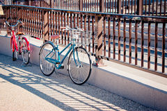 Bicycle park at the railing on the road Stock Image