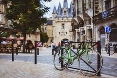 Bicycle parked against railing in Bordeaux with Port Cailhau in stock photography