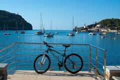 Bicycle parked against railing in front of moored boats and horizon. SOLLER, MALLORCA, SPAIN - SEPTEMBER 28, 2018: Bicycle parked against railing in front of royalty free stock photography
