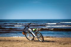 Bicycle parked on Baltic beach next to water in spring. Bicycle parked next to water on Baltic beach in early spring royalty free stock image