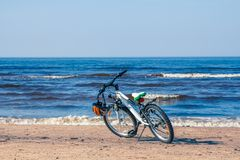 Bicycle parked on Baltic beach next to water in spring. Bicycle parked next to water on Baltic beach in early spring stock images
