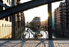 Bicycle parked on bridge above water aganst Hamburg cityscape Stock Photography