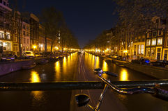Bicycle parked on bridge in Amsterdam at night Stock Photography