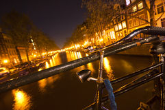 Bicycle parked on bridge in Amsterdam at night Royalty Free Stock Photos