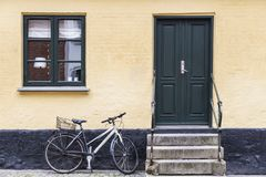 Bicycle parked at the door of a home on a street in a Danish cit stock photo