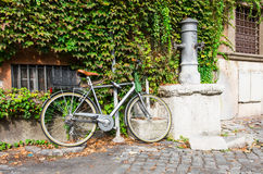 Bicycle parked near drinking tap on the street in Rome Royalty Free Stock Image