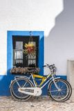 Bicycle parked near house. Typical european view of a bicycle parked near house painted with blue and flower vases royalty free stock images