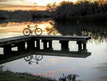 Bicycle parked on pier with sunset. Bike on pier reflecting off of water with sunset Royalty Free Stock Images