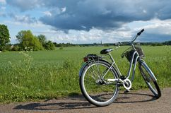 Bicycle parked on roadside beside field: Sweden. Bicycle resting on the road side, overlooking lush green grasslands and farming area, outside Uppsala, Sweden royalty free stock images