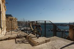 Bicycle parked on the shore of the harbor on a beautiful sunny day in Gallipoli - Salento Stock Photo