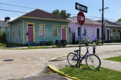 Bicycle parked at a stop sign in front of a row of colorful houses in a street of the city of New Orleans in Louisiana. New Orleans, Louisiana, USA - June 17 royalty free stock photography