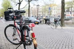Bicycle parked on the street in the foreground with a typical canal and architecture of Amsterdam, Netherlands. Slightly out focus on the background during royalty free stock image