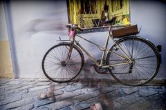 Bicycle parked in the street, silhouette blurred Stock Image