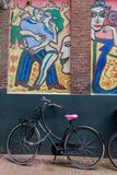 Bicycle parked under a modern painting of man and woman dancing