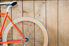 Bicycle parked with wood wall, close up image. Orange bicycle parked with wood wall, close up image part of bicycle stock photography