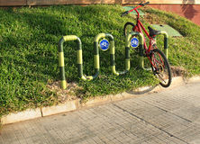 Bicycle Parking. A red bicycle parked on grass in a bicycle parking space Stock Images