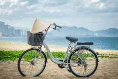 Bicycle parking in the beach sand. on handlebars Vietnamese hat hanging. Vietnam Stock Images