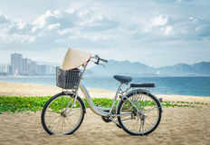 Bicycle parking in the beach sand. on handlebars Vietnamese hat hanging. Vietnam Royalty Free Stock Images