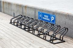 Bicycle parking of black color. The bicycle parking from metal of black color on a wooden flooring for safe fixing of wheel vehicles, with sign free parking Stock Photos