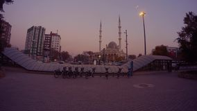 Bicycle parking in the evening, mosque and minarets, high-rise modern houses in the center of Konya stock video
