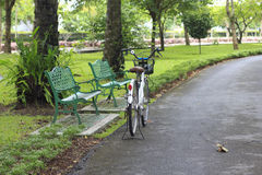 Bicycle parking near the chair in the garden Royalty Free Stock Image