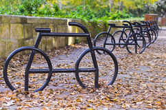 Bicycle parking racks. A series of bicycle parking racks in the midst of dried leaves during winter Stock Photos