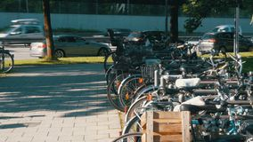 Bicycle Parking in the Street of Munich. A lot of bicycles stand in the parking lot against the background of passing cars on the road stock video footage