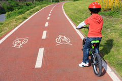Bicycle path. Child with helmet on bicycle path Royalty Free Stock Photos