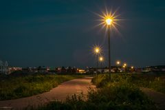 Bicycle path with bright lanterns in Holland at night royalty free stock photography