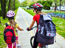 Bicycle path with children. Girls wearing helmet with rucksack . Royalty Free Stock Photography