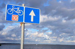 Bicycle path sign nr ten near lake and cloudy sky. Royalty Free Stock Photos