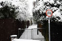 Bicycle path with sign in snow. Snowy bike path alleyway with snow and a bike sign Royalty Free Stock Photo