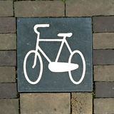 Bicycle paving stone. Painted picture of a bicycle on a paving slab surrounded by bricks with space for text Stock Photos