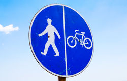 Bicycle and pedestrian lane sign against the blue sky Royalty Free Stock Image
