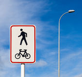 Bicycle and pedestrian shared route sign on pole post against bl Stock Photography